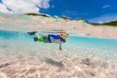 Natación del niño pequeño en el océano fotos de archivo