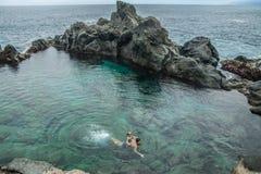 Natación del padre y de la hija en la piscina natural Charco De La Laja, en el norte de Tenerife Imagen de archivo