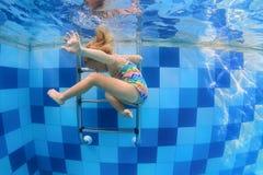 Natación del pequeño niño con la diversión y salto abajo en piscina Imagen de archivo