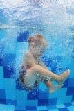 Natación del pequeño niño con la diversión y salto abajo en piscina foto de archivo