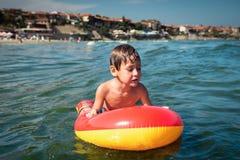 Natación del pequeño niño en el mar en el colchón inflable y la mirada con cautela Fotografía de archivo libre de regalías