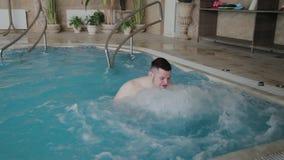 Natación divertida alegre del hombre en piscina del Jacuzzi almacen de metraje de vídeo