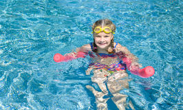 Natación feliz de la niña con tallarines rosados de la espuma en un whi de la piscina Fotos de archivo libres de regalías