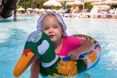 Natación feliz de la niña en el pato inflable fotografía de archivo