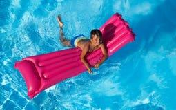 Natación feliz del muchacho en el colchón inflable rosado foto de archivo