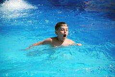 Natación feliz del muchacho en la piscina Fotografía de archivo libre de regalías