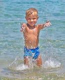 Natación feliz del niño en el mar Fotos de archivo