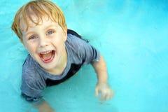 Natación feliz del niño en piscina Imagen de archivo libre de regalías