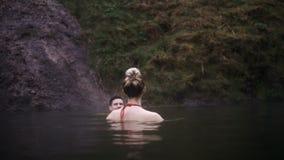 Natación feliz joven de la mujer en las aguas termales junto Hombre y mujer que viajan en valle de las montañas en Islandia almacen de metraje de vídeo
