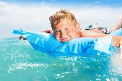Natación fresca linda del muchacho en el colchón en el mar Fotografía de archivo libre de regalías