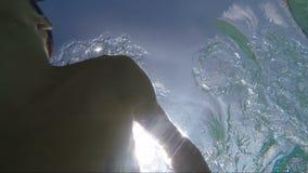 Natación hermosa del hombre joven en la piscina, tiro subacuático almacen de metraje de vídeo