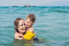 Natación joven de la madre y el jugar con el muchacho del niño masculino en el mar o Imagen de archivo libre de regalías