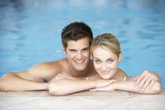 Natación joven de los pares en piscina fotos de archivo