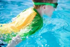 Natación joven del muchacho en la piscina Imagenes de archivo