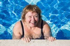 Natación mayor activa de la mujer en agua azul de la piscina Foto de archivo libre de regalías