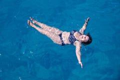 Natación mayor activa de la mujer en agua de mar azul Imagen de archivo