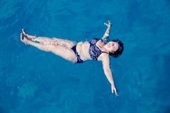 Natación mayor activa de la mujer en agua de mar azul Fotografía de archivo libre de regalías