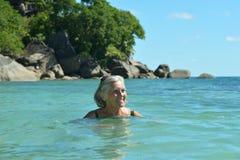 Natación mayor de la mujer en el mar foto de archivo