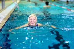 Natación mayor de la mujer en piscina Fotografía de archivo libre de regalías