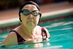 Natación mayor de la mujer en una piscina Imágenes de archivo libres de regalías