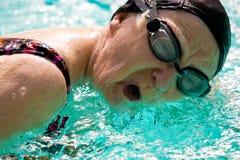 Natación mayor de la mujer en una piscina Foto de archivo libre de regalías