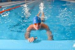 Natación profesional del hombre con el sombrero y las gafas en la piscina foto de archivo libre de regalías