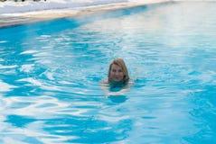 Natación rubia joven de la mujer en piscina del aire libre en el invierno Imagenes de archivo
