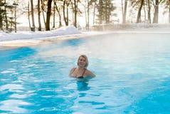 Natación rubia joven de la mujer en piscina del aire libre en el invierno Fotografía de archivo