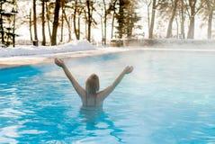 Natación rubia joven de la mujer en piscina del aire libre en el invierno Foto de archivo