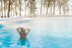 Natación rubia joven de la mujer en piscina del aire libre en el invierno Fotos de archivo