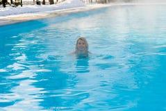 Natación rubia joven de la mujer en piscina del aire libre en el invierno Foto de archivo libre de regalías