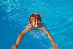 Natación sonriente del muchacho en una piscina Foto de archivo libre de regalías