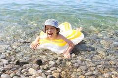 Natación sonriente feliz del muchacho con swimmring en el mar imagen de archivo libre de regalías