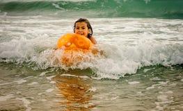 Natación de la niña con la bola en el océano en las ondas Foto de archivo libre de regalías