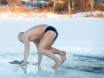 Natación del invierno Hombre a un hielo-agujero Foto de archivo libre de regalías
