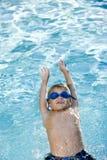 Natación del muchacho en el suyo detrás en piscina Foto de archivo