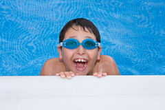 natación del muchacho en la piscina con anteojos y un g grande Imagen de archivo