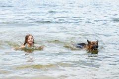 Natación del pastor alemán y de la muchacha en el lago Fotos de archivo