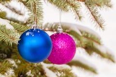 A Natal-árvore azul e roxa brinca nos ramos nevado imagens de stock royalty free