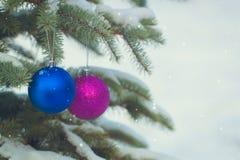 A Natal-árvore azul e roxa brinca nos ramos nevado imagem de stock