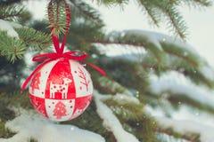 A Natal-árvore vermelha do estilo escandinavo brinca nos ramos nevado fotos de stock royalty free