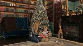 Natal aberto da mamã e do filho perto da árvore de Natal vídeos de arquivo