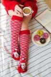 Natal acolhedor em casa Pés do ` s das mulheres em meias do Natal, no presente grande, no copo do chá, nos doces e no chocolate d Imagens de Stock