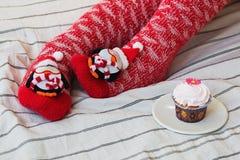 Natal acolhedor em casa Pés do ` s das mulheres em meias do Natal, no presente grande, no copo do chá, nos doces e no chocolate d Foto de Stock Royalty Free
