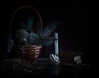 Natal, ano novo cesta com ramos e cones do abeto em um fundo escuro Foto de Stock Royalty Free