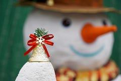 Natal Bell dourada com fundo do boneco de neve para o conceito do Natal Fotos de Stock Royalty Free