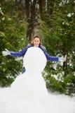 Natal branco A jovem mulher bonito constrói um boneco de neve grande no parque Imagens de Stock