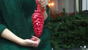 Natal, decoração, feriados e conceito dos povos - fim acima da mão da mulher que guarda o cone vermelho do Natal vídeos de arquivo
