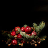 Natal e ano novo Maçãs com cones do pinho e porcas no bas Imagens de Stock