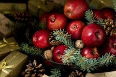 Natal e ano novo Maçãs com cones do pinho e porcas no bas Foto de Stock